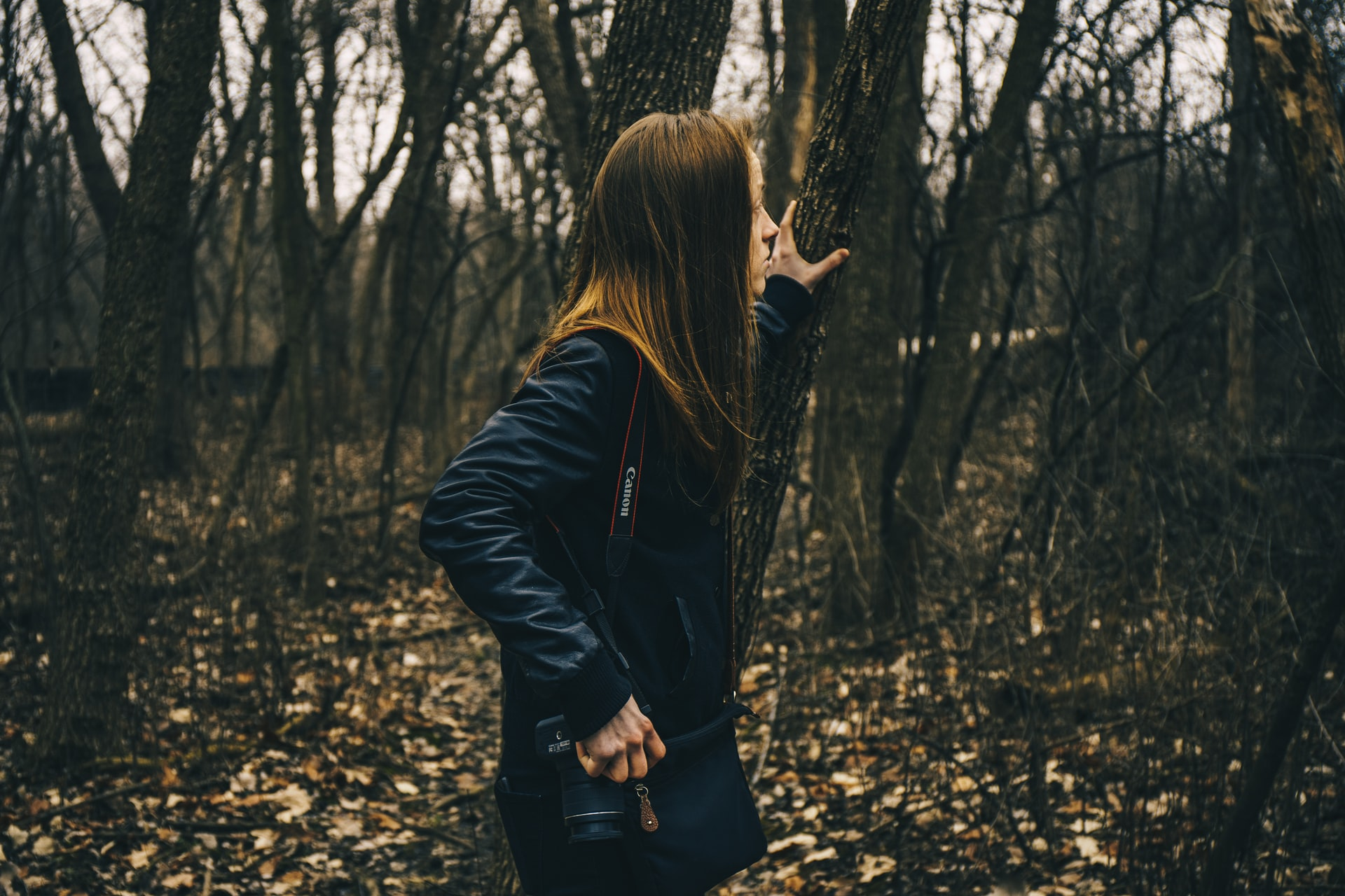 example of photographic storytelling; person wandering through woods, looking apprehensive