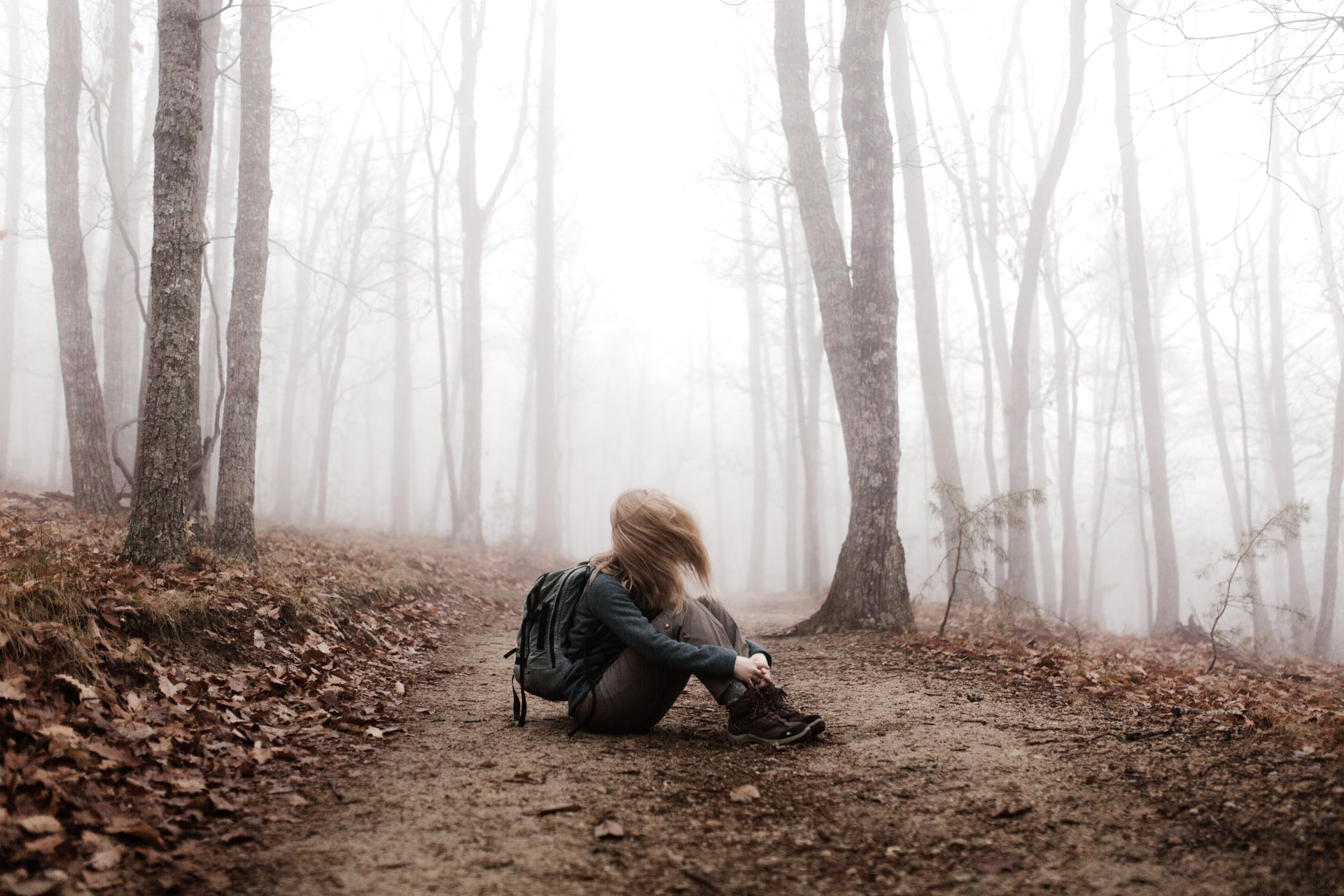 photographic storytelling; person sitting on floor alone in misty forest