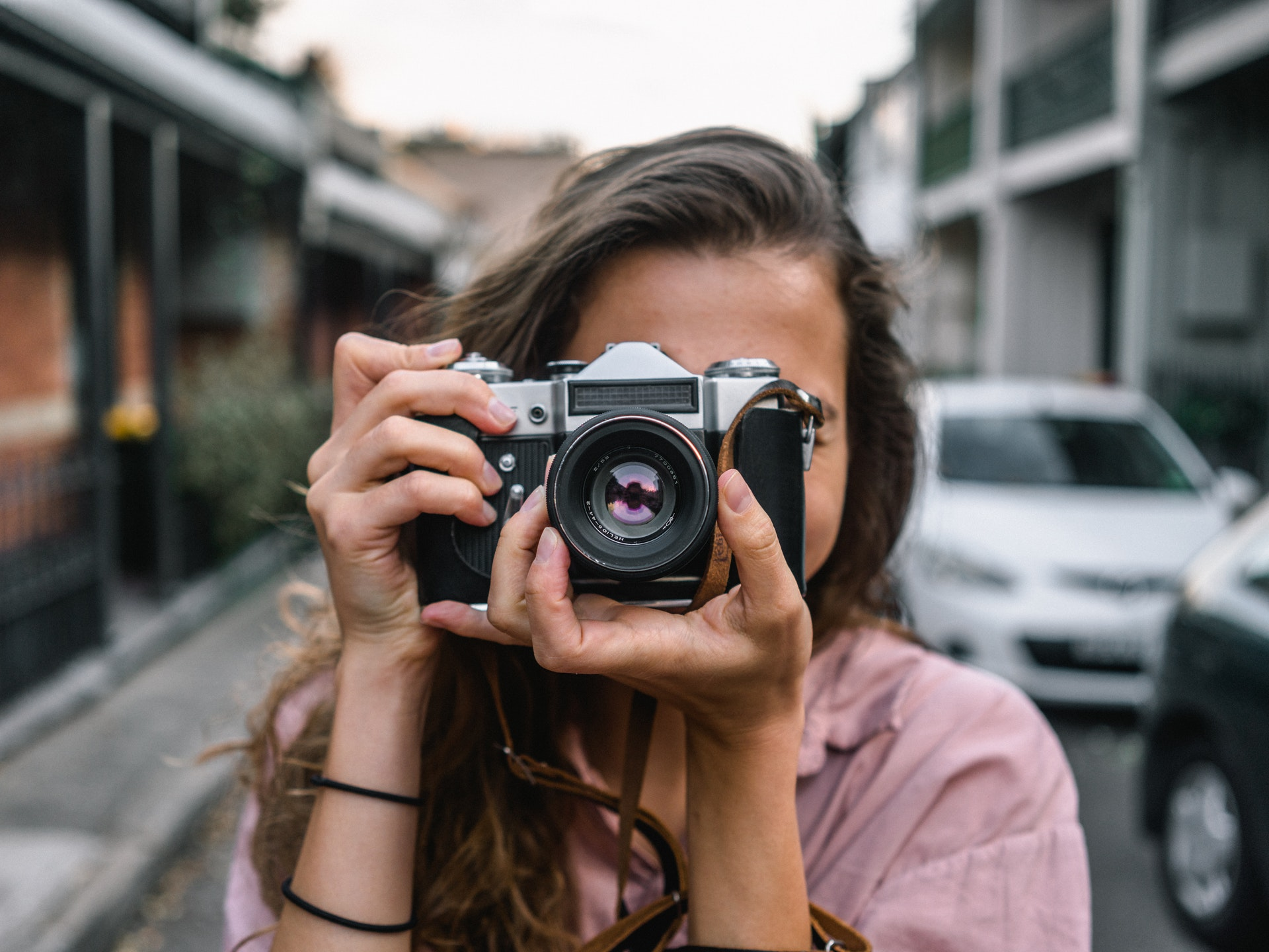 person holds mirrorless camera pointed at viewer, urban background, what is a mirrorless camera?