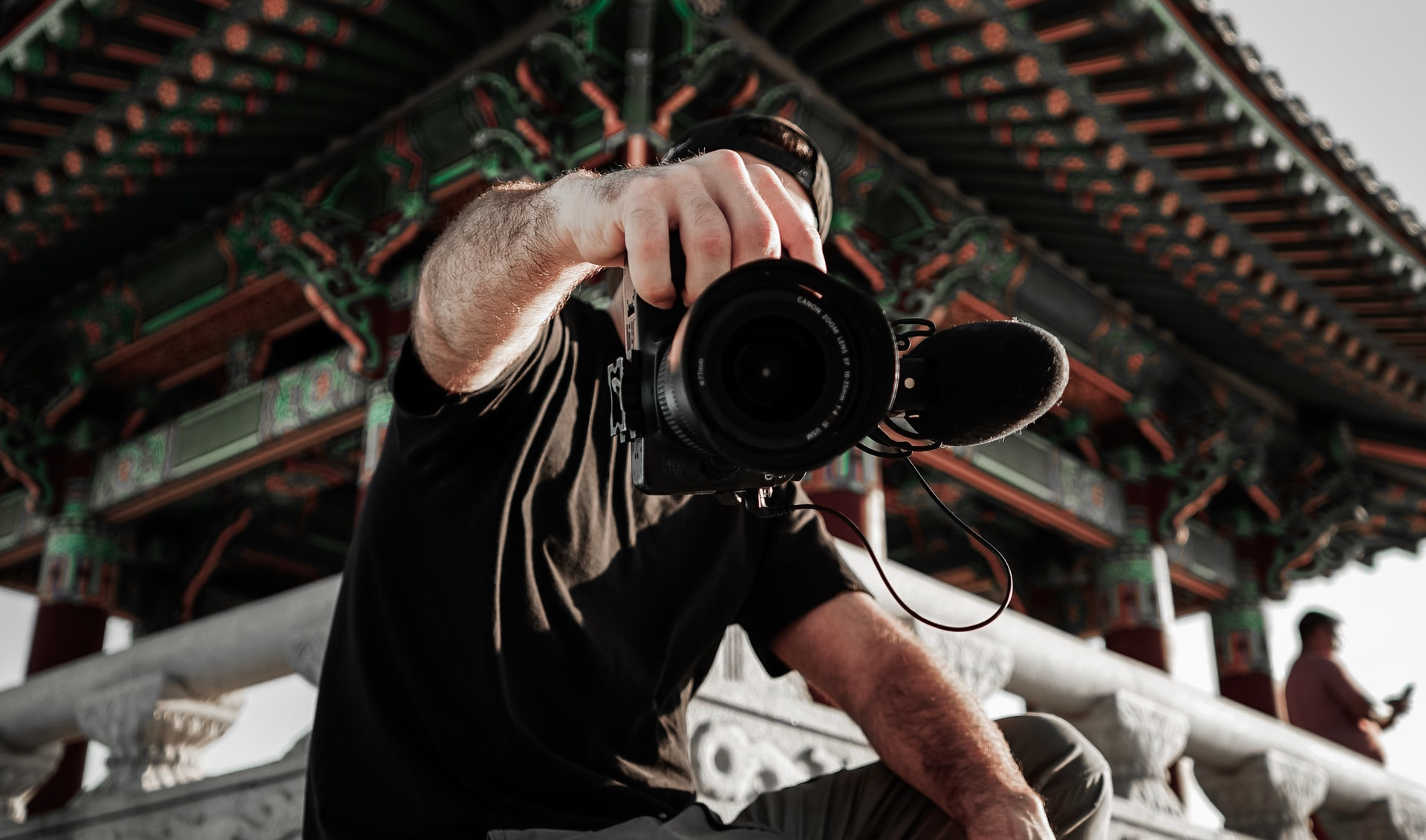 vlogger holds his dslr camera to the viewer, crouched in front of an oriental structure