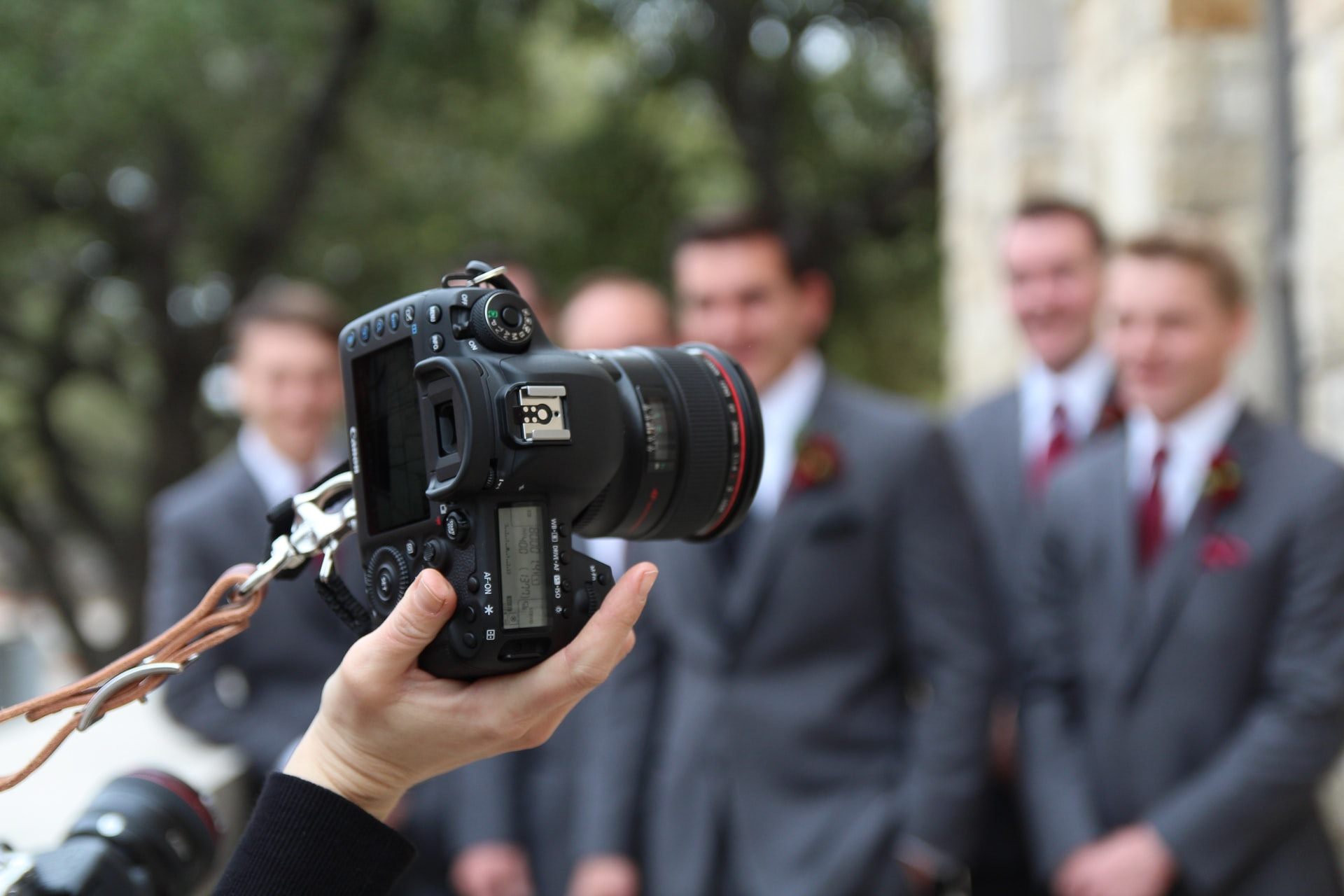 dslr camera in focus, camera in photographer's hand, wedding guests in background