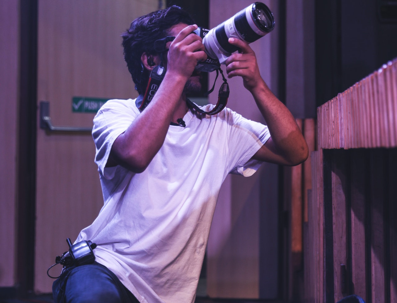 event photographer crouched by stage taking photo with DSLR camera, photography career