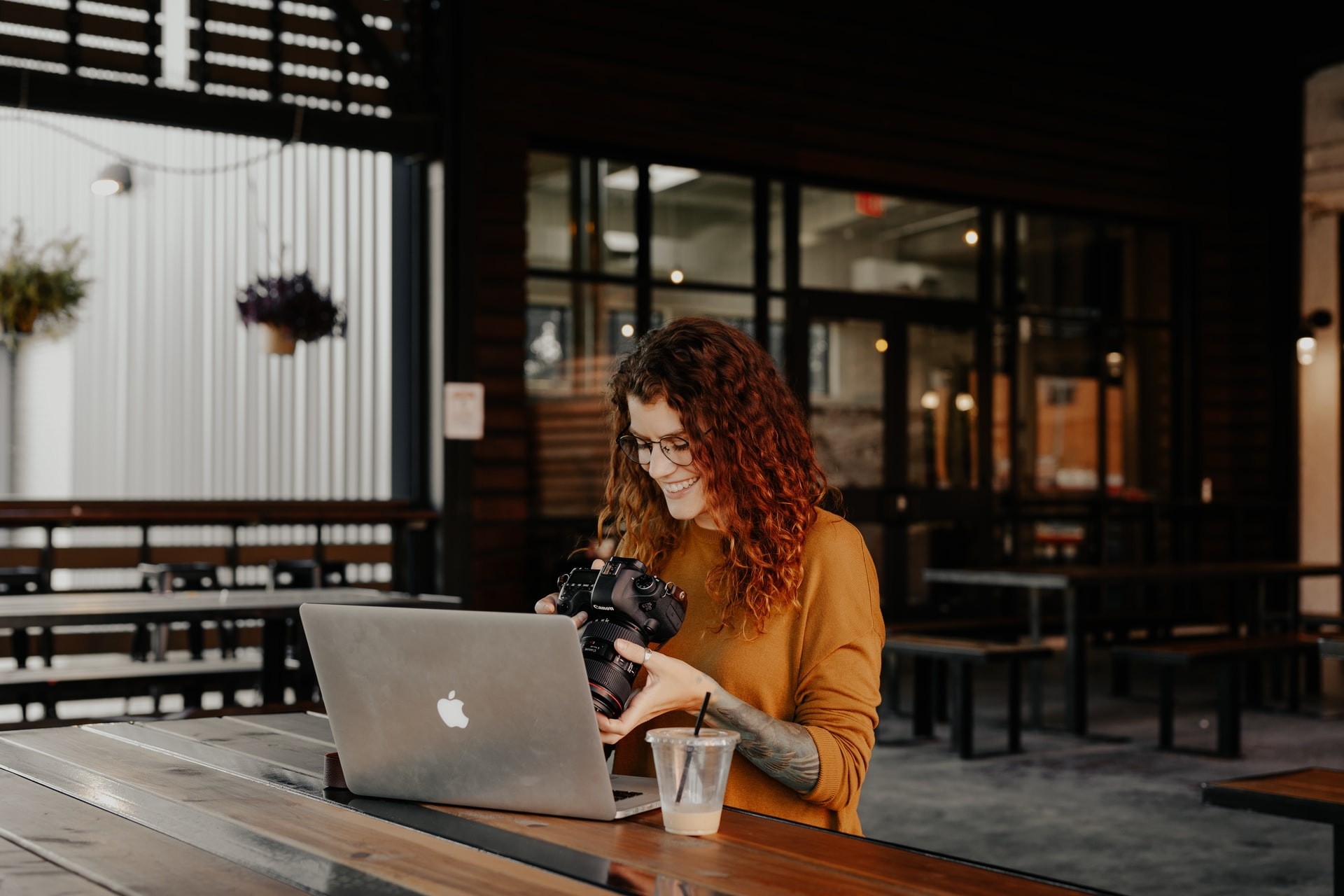 red-haired person with glasses, tattoos and orange top sits at her mac, holding a DSLR camera, photography blogger