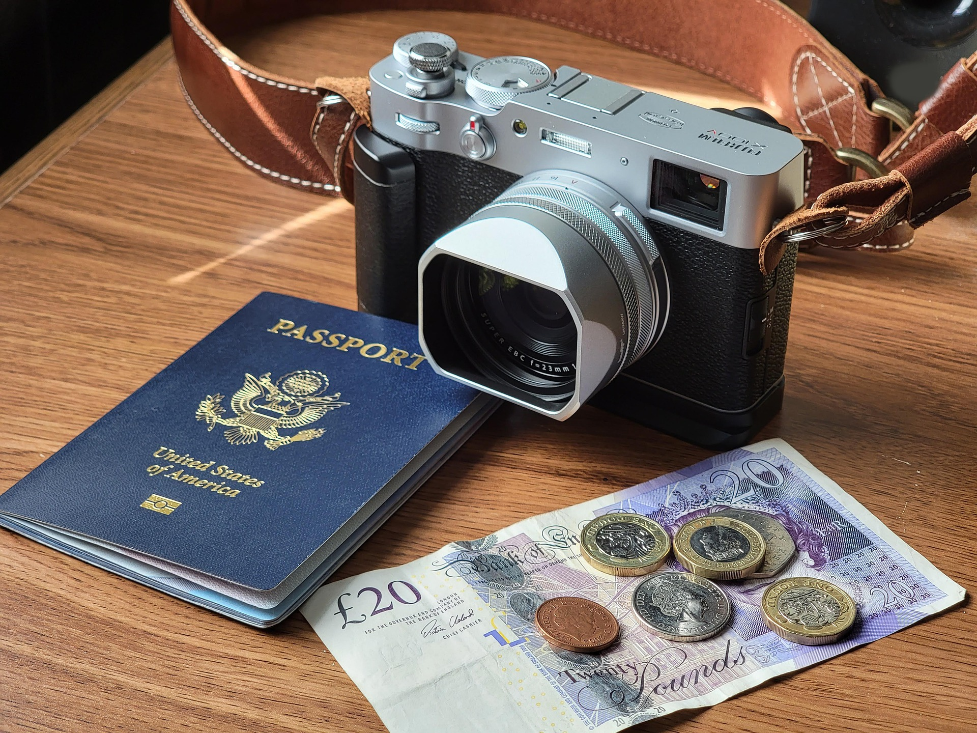 camera sits on table beside money and a passport
