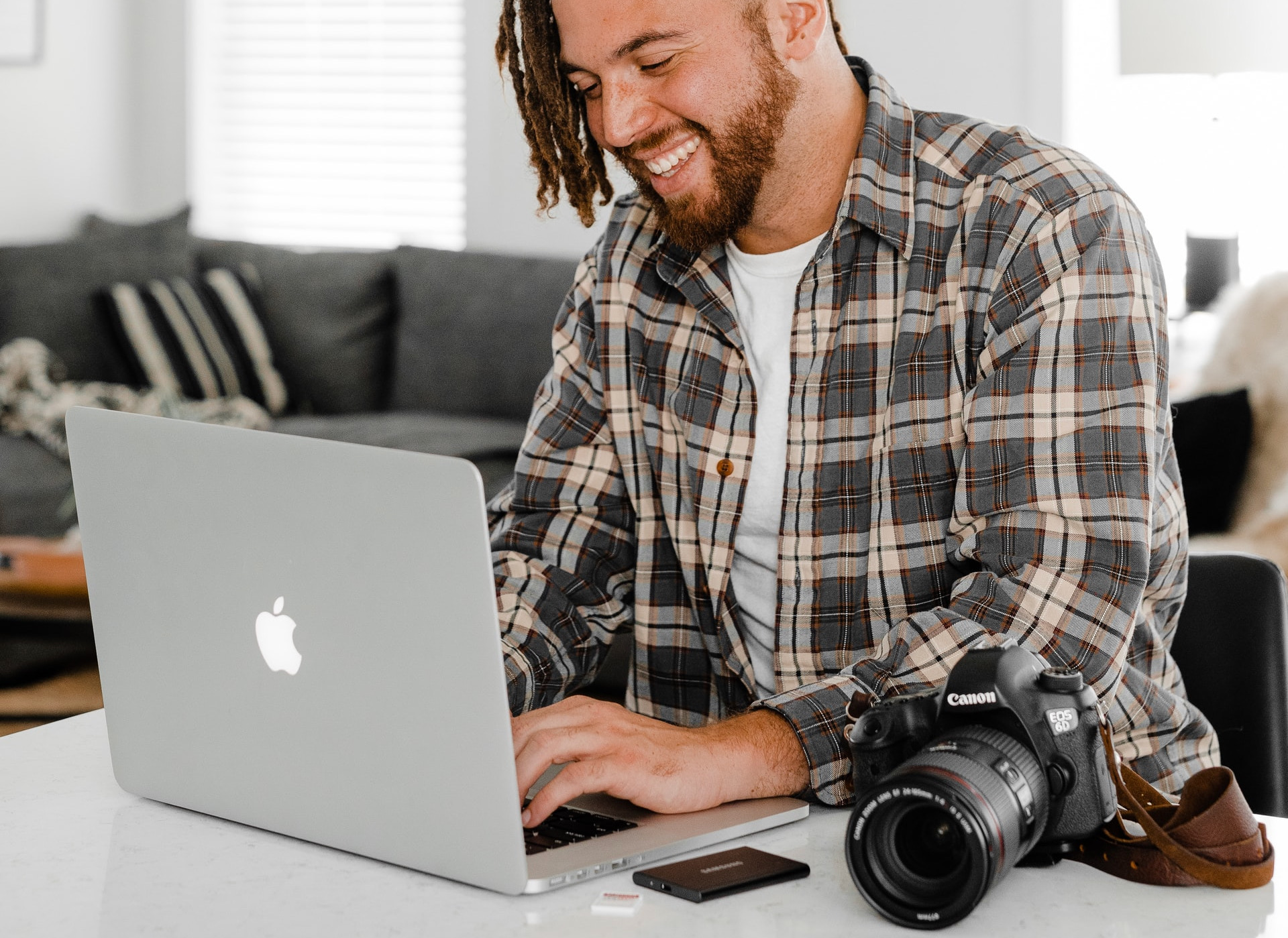 photography blogger sits at his mac, typing, dslr camera on the table beside him