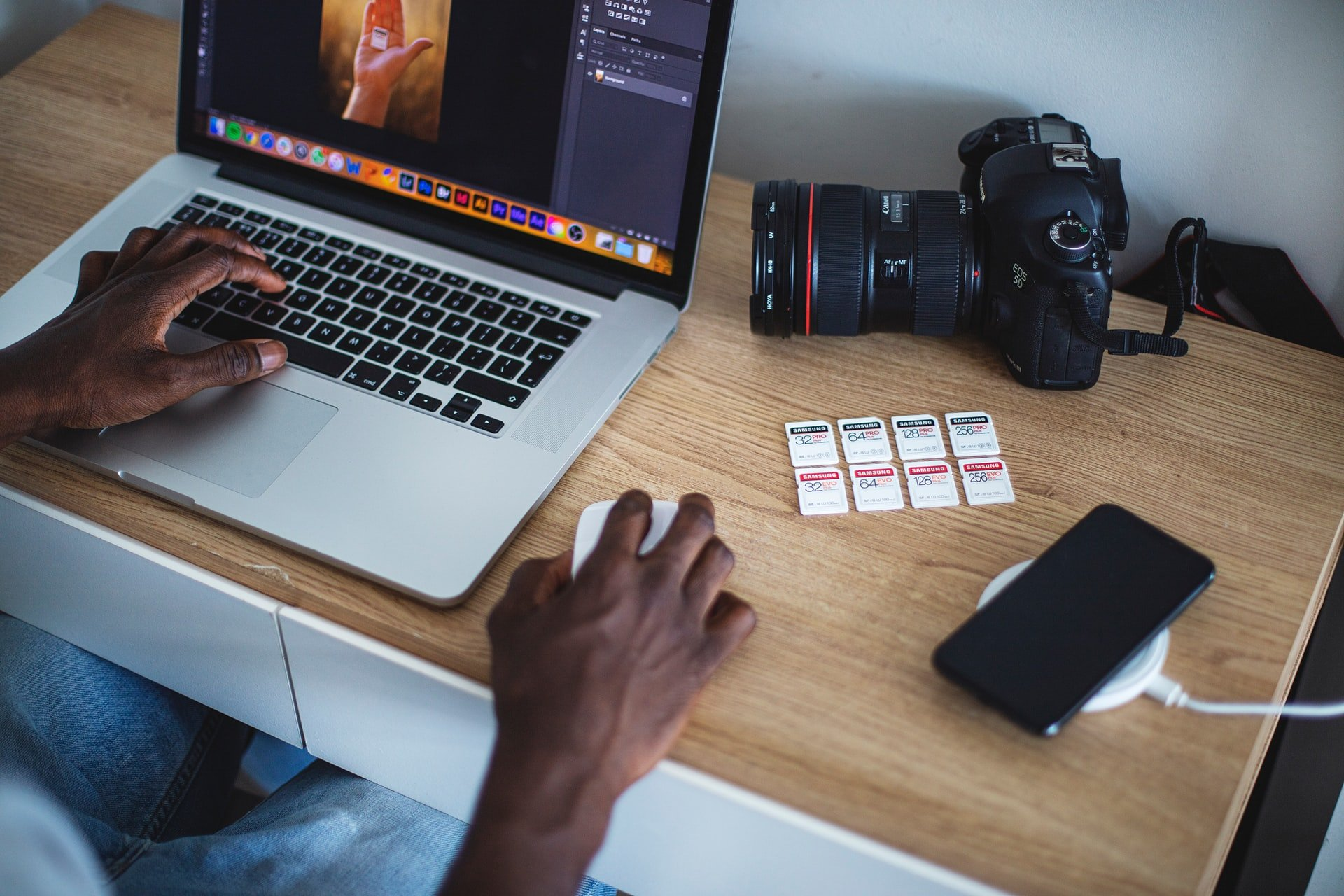 person working at computer, editing photos, dslr camera on table with smartphone