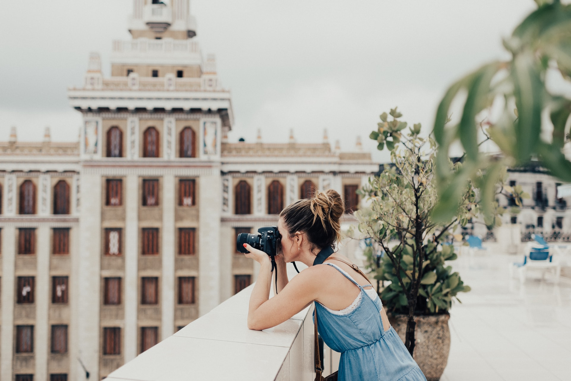 travel photographer taking scenic photo with DSLR camera