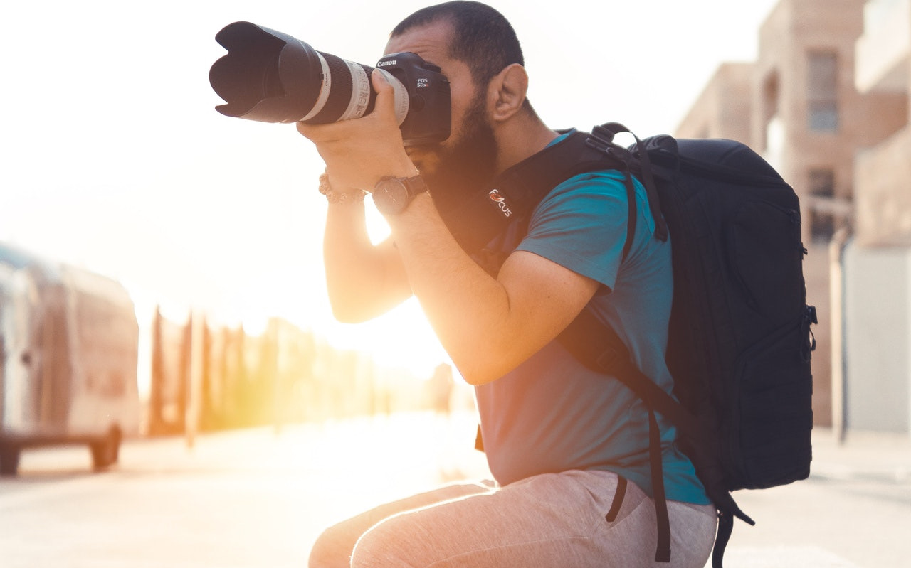 photographer using DSLR camera with large lens, camera bags