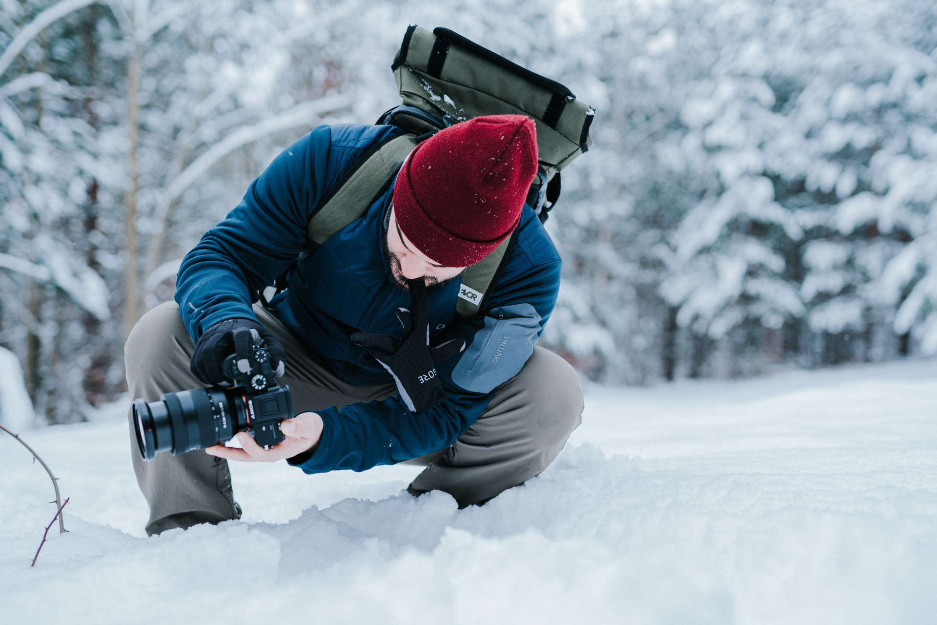 photographer crouched down in the snow taking a pro photo, instagram photography camera advice