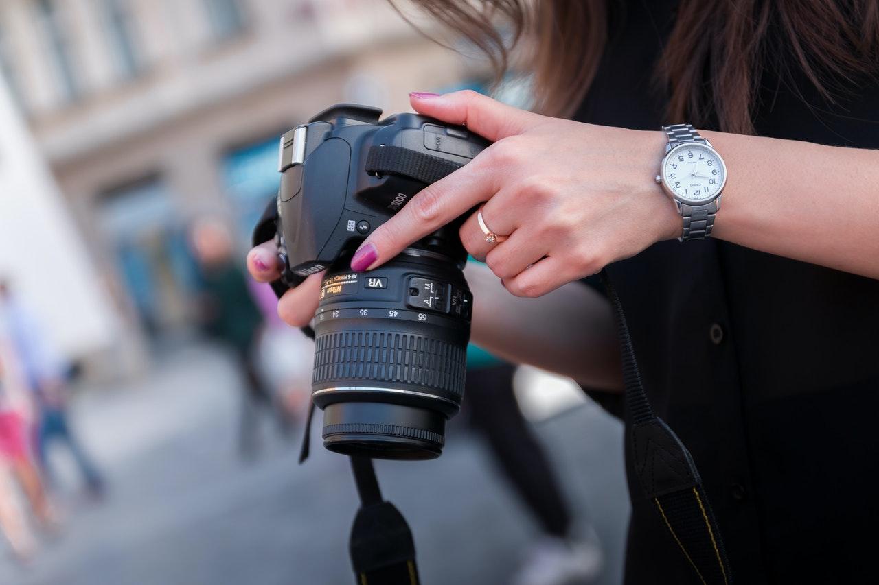 closeup of person holding a DSLR camera, how do DSLRs work?
