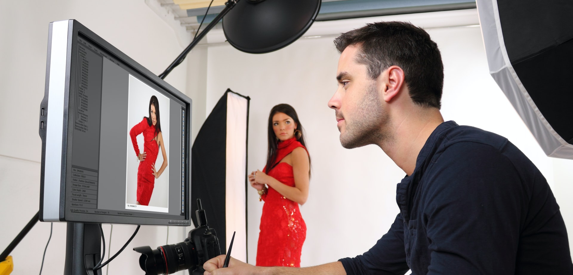 photographer sits at computer editing RAW photo of model who is posing in set in background