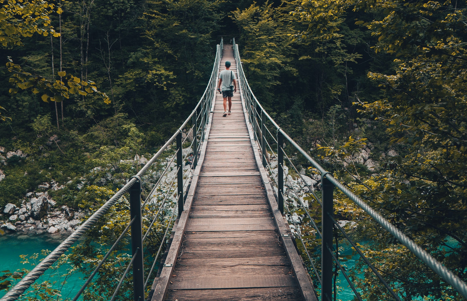 person walking away from camera on a bridge surrounded by river and trees, example of leading lines in photography