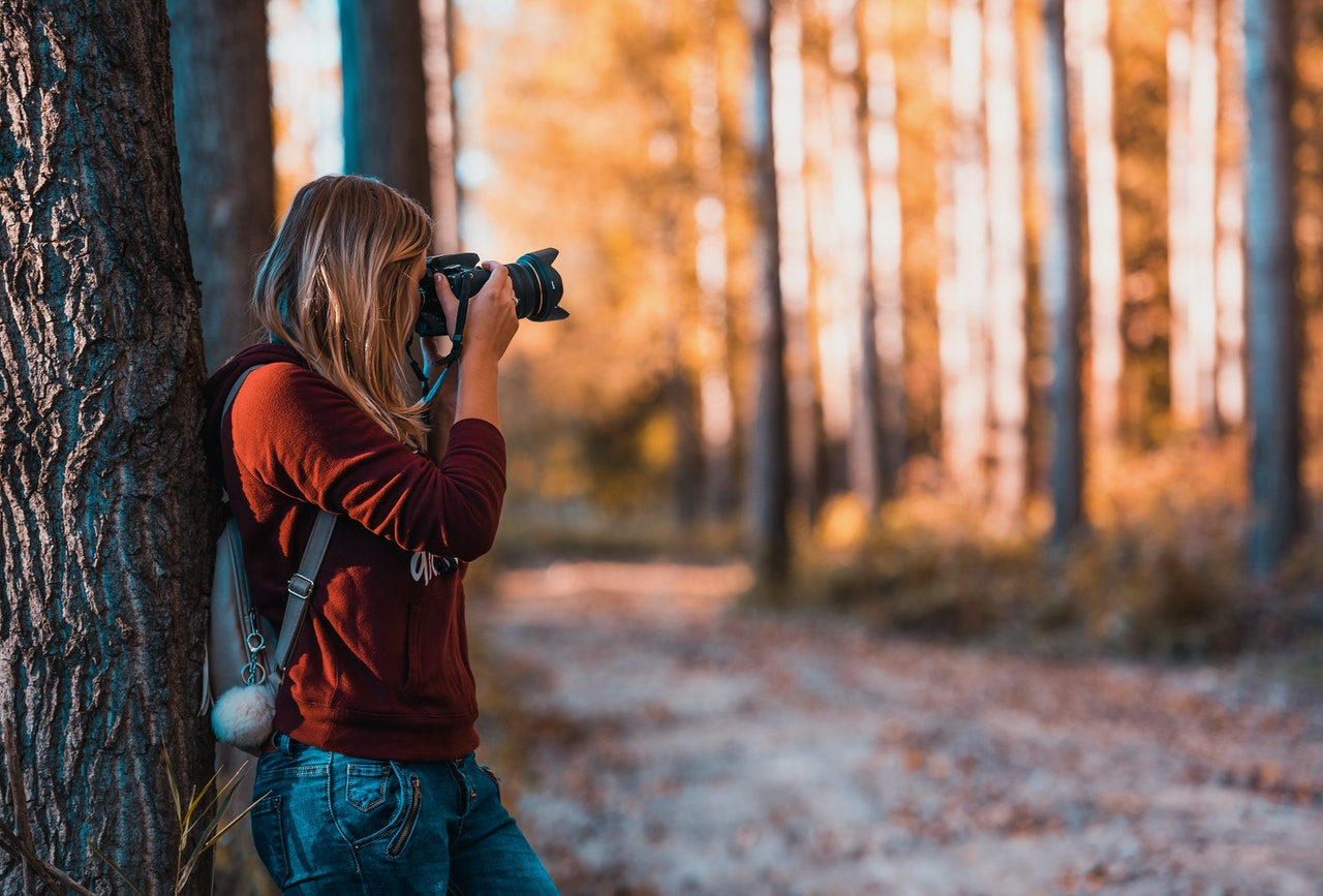 photographer leans against a tree in autumn, taking RAW photos with DSLR camera