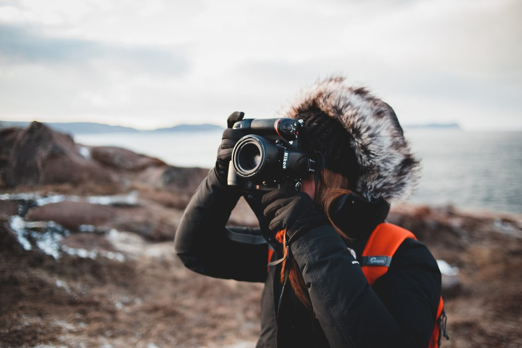 photographer wrapped up warm taking RAW photos outside