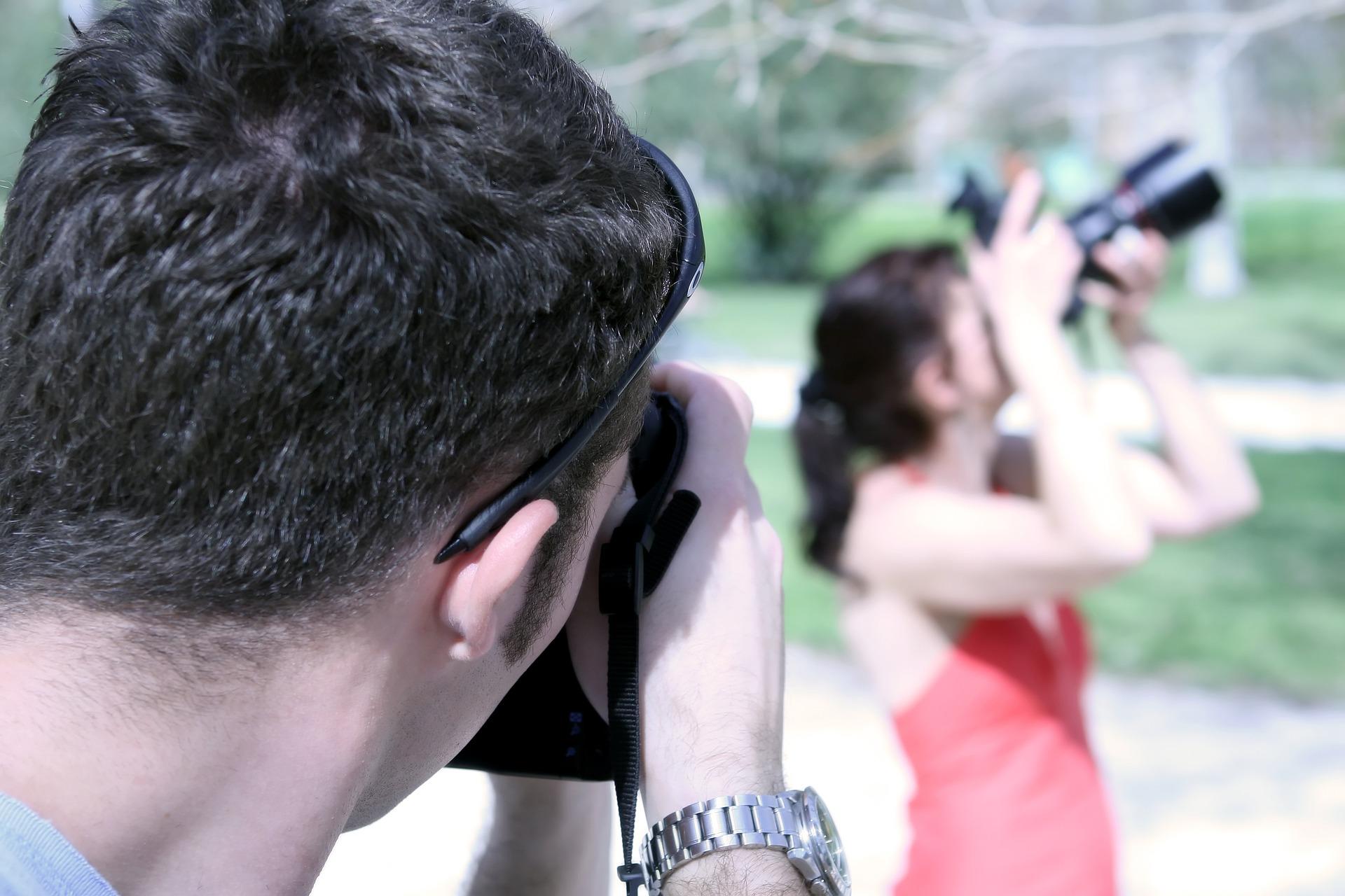 closeup behind photographer taking photo of woman using a DSLR camera