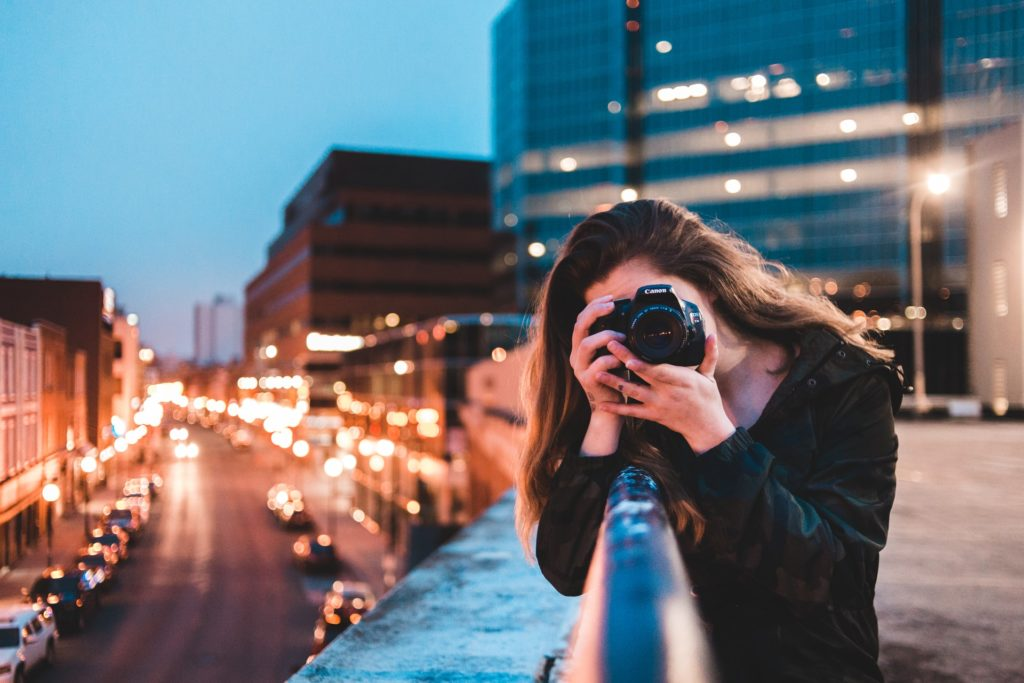 female photographer facing the viewer from behind her lens, standing in a city above well-lit road